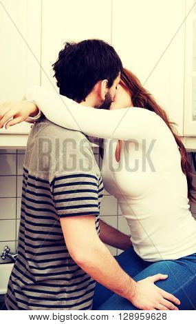 Romantic couple kissing in the kitchen.