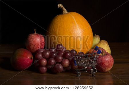 variety of fruits and a small shopping cart on a woden table, studio picture