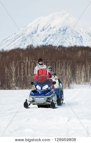 KAMCHATKA RUSSIA - FEB 5 2012: Snowmobile with tourists and travelers sitting in the sleigh rides on the background of a winter forest and active Koryak Volcano. Eurasia Russian Far East Kamchatka Region.