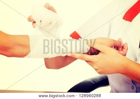 Young smile woman doctor bandaging female hand
