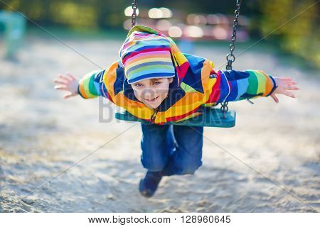 Preschool kid boy having fun with chain swing on outdoor playground. child swinging on warm sunny spring or autumn day. Active leisure with kids. Boy wearing colorful clothes