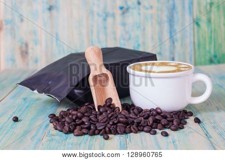 package of coffee beans and hot latte art on the wooden table