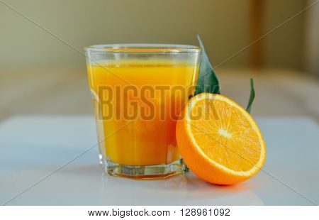 Freshly squeezed orange juice in a small glass with sliced orange.