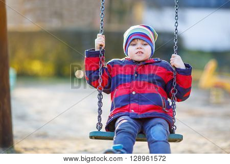toddler little kid boy having fun with chain swing on outdoor playground. child swinging on warm sunny spring or autumn day. Active leisure with kids. Boy wearing colorful clothes