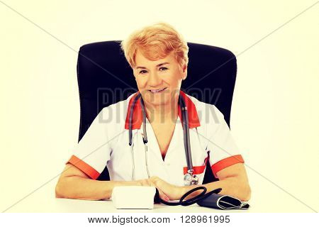 Smile elderly female doctor or nurse sitting behind the desk with bloog preasure gauge
