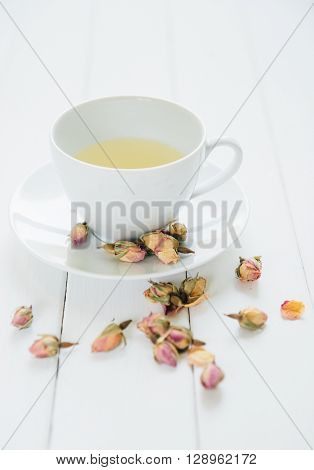 Rose flavoured tea in a white cup with dry rose buds scattered around on white background.