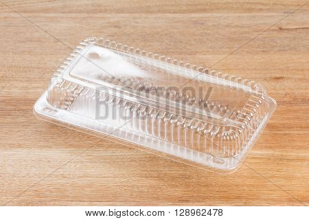 Empty transparent plastic storage box of food package on wooden background