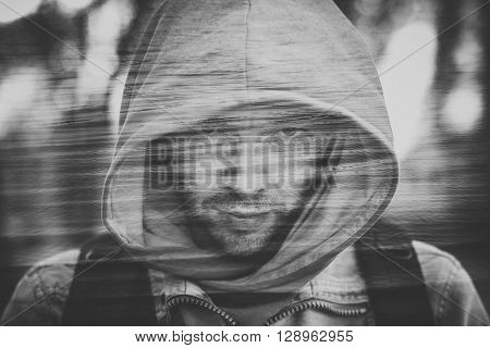 Close-up portrait of threatening gangster wearing a hood representing the concept of danger. Close-up portrait of threatening gangster wearing a hood representing the concept of danger