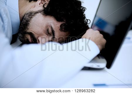 Tired businessman sleeping on his computer