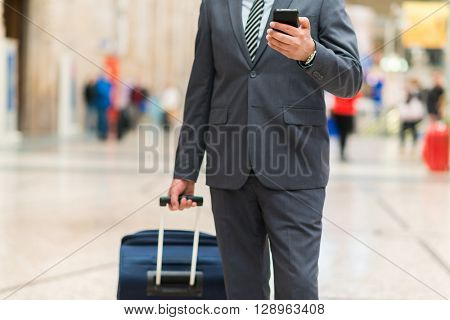Man walking in a train station using his smartphone