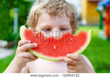 Adorable little toddler boy with blond hairs eating watermelon in summer garden. Kid tasting healthy snack. Selective focus on watermelon