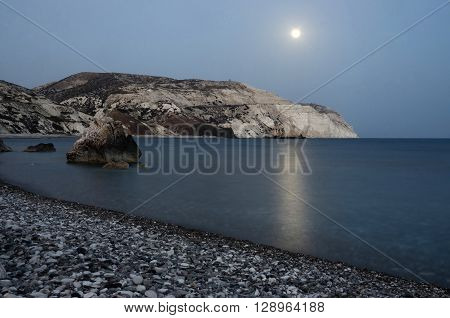 Night seascape of Aphrodite's Rocks beach with moon shine bithplace of greek goddess of love Paphos Western Cyprus also called Petra tou Romiou, famous landmark