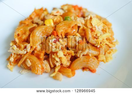 macaroni pasta in tomato sauce on a wooden table