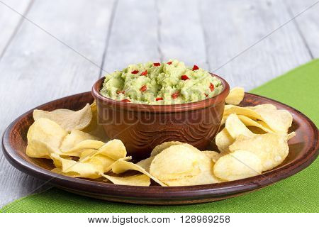 bowl of guacamole dip and potato chips on a clay brown dish on a green table mat with slice of lime on a white wooden background