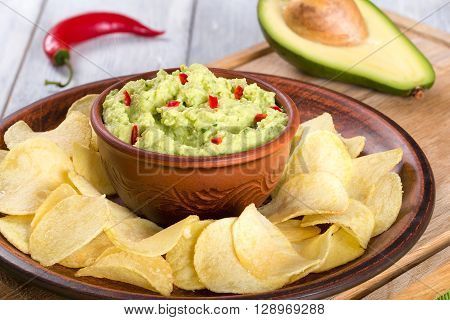 bowl of guacamole dip and potato chips on a clay brown dish on a green table mat with slice of lime on a white wooden background close-up