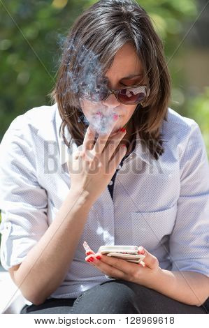 Portrait of brunette smoking cigarette while looking at cell