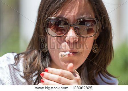 Close-up of brunette in sunglasses lightning cigarette