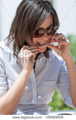 Close-up of adult woman in sunglasses making handmade cigarette