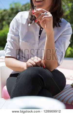 Close-up of smiling unrecognizable woman smoking cigarette