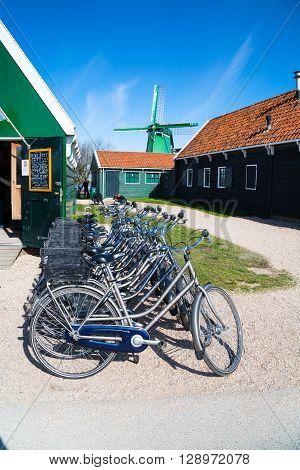 Zaanse schans, Netherlands - April 1, 2016: Bikes for rent, windmill in Zaanse Schans, traditional village, Netherlands, North Holland, green houses against blue cloudy sky