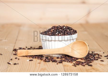 Rice berry in bowl on wood background