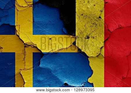 flags of Sweden and Belgium painted on cracked wall