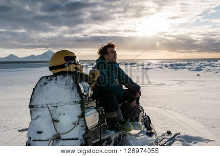 Man sitting on a snowmobile waiting for the rest of the team, Spitsbergen
