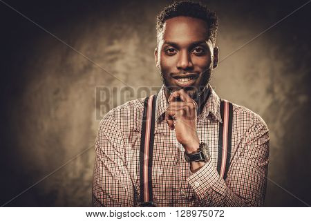 Stylish young black man with suspenders posing on dark background.