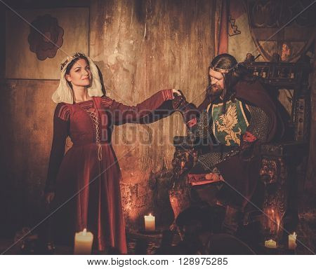 Medieval king with his queen in ancient castle interior.