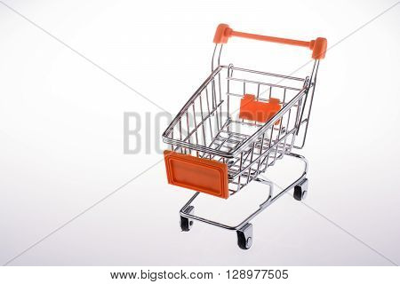 Orange color shopping cart in white background