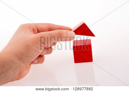 Hand making house with colorful cubes on a white background