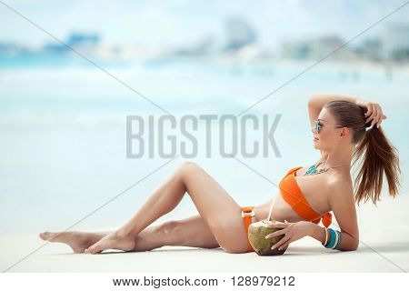 Young beautiful brunette woman with long straight hair,mirrored sun glasses,blue, slim figure,wearing around his neck a large necklace,on the left arm-bracelets, spends time on a tropical beach on the white sands in an orange bikini near blue ocean