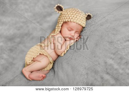 Newborn baby brown knitted cap with black ears, sleeping sweetly on a soft gray blanket,tucked under his legs and put the handle under my cheek