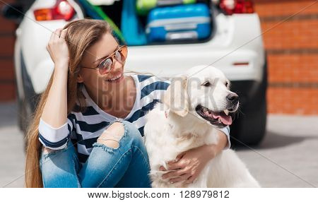 Beautiful young woman brunette with long hair,a beautiful smile,wearing sun glasses, dressed in a t-shirt with white and dark blue stripes,blue jeans with holes in the knees,sits with his white dog near a white car loaded with stuff