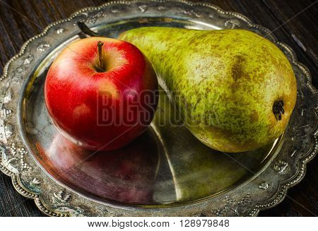 Pear and apple on a vintage plate, wooden background, closeup