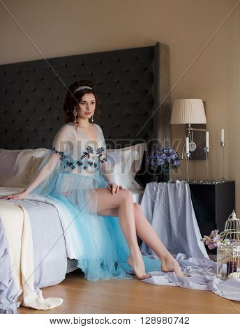Beautiful young woman with brown eyes,brunette with beautiful wedding hairstyle with tiara, ears expensive earrings,sitting on the bed near the curtained window, the white curtains in the hotel room,dressed in a transparent robe of blue,bare feet