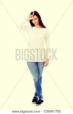 Young woman making a looser sign