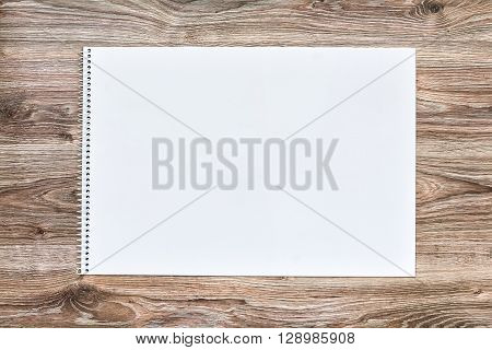 Mockup of open album with blank white page on wooden background. Gorizontal orientation, top view.