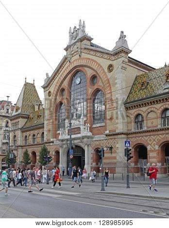 BUDAPEST HUNGARY - JULY 13: Shoppers in Front of Central Market Hall in Budapest on JULY 13 2015. Great Market Hall at Fovam Square With People and Traffic in Budapest Hungary.