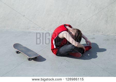 Young Man Fall Off  Skate Board, Sitting On Concrete Ramp.
