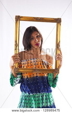 young beautiful woman inside an antique picture frame (isolated on gray)
