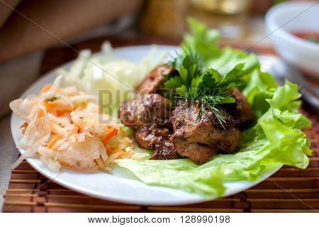 grilled shashlik with pickled cabbage and salad and fragrant herb