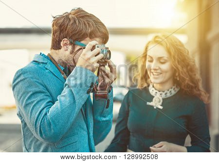 Hipster man wants to take a picture of a beautiful girl using your vintage camera