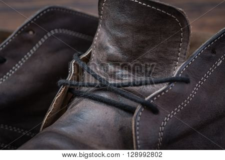 Old Worn Out Brown Leather Shoes Over The Dark Background
