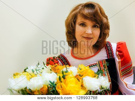 Portrait of fifty well-groomed woman in Russian folk costume with a bouquet of flowers