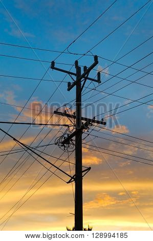Electric lines against colorful sunset sky
