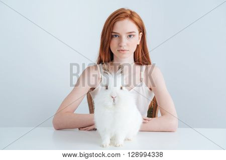 Beautiful redhead woman sitting at the table with rabbit isolated on a white background