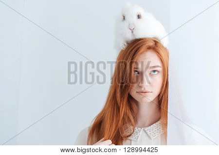 Portrait of a beautiful redhead woman posing with rabbit on her head isolated on a white background