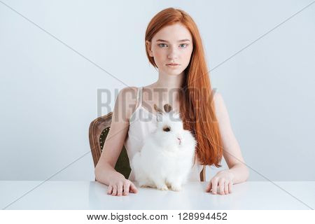 Charming redhead woman sitting at the table with rabbit and looking at camera isolated on a white background