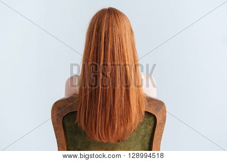 Rear view portrait of a redhead woman sitting on the chair isolated on a white background